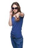 Mujer que señala en la cámara mientras que habla en el teléfono celular Imagen de archivo