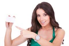 Mujer que señala en la tarjeta en blanco Imagen de archivo