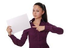Mujer que señala en una tarjeta en blanco Imagen de archivo