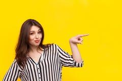 Mujer que señala lejos en amarillo Imagen de archivo
