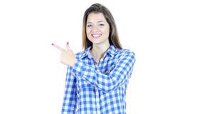 Mujer que señala mostrando el producto a un lado, fondo blanco, jóvenes, metrajes
