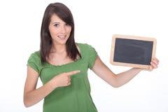 Mujer que señala una pizarra Imagen de archivo