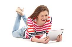 Mujer que se acuesta con la tableta digital Foto de archivo