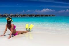 Mujer que se acuesta con las aletas y la máscara que bucean en una playa tropical Imagen de archivo libre de regalías