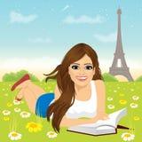 Mujer que se acuesta en el libro de lectura de la hierba Imagen de archivo