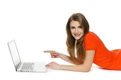 Mujer que miente en el piso con su ordenador portátil Fotografía de archivo libre de regalías