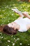 Mujer que se acuesta en hierba con el libro Fotografía de archivo