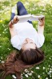 Mujer que se acuesta en hierba con el libro Fotos de archivo libres de regalías