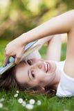 Mujer que se acuesta en hierba con el libro Imagen de archivo