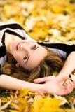 Mujer que se acuesta en hojas de otoño Foto de archivo libre de regalías