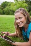 Mujer que se acuesta en un parque mientras que usa su tablilla Imagenes de archivo