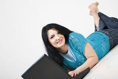 Mujer que se acuesta y que usa la computadora portátil Imagen de archivo
