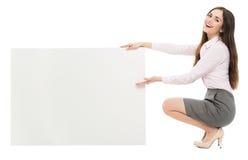 Mujer que se agacha al lado de tablero en blanco Fotografía de archivo