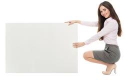 Mujer que se agacha al lado de tablero en blanco Imagenes de archivo