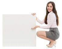 Mujer que se agacha al lado de tablero en blanco Foto de archivo