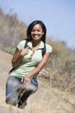 Mujer que se agacha en la sonrisa del camino de la playa Imagenes de archivo