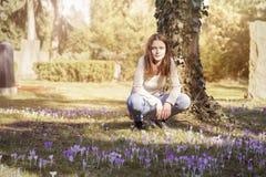 Mujer que se agacha en un prado de la flor de la primavera Imagen de archivo