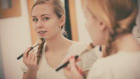 Mujer que se aplica con la máscara del fango de la arcilla del cepillo a su cara Fotos de archivo libres de regalías