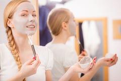Mujer que se aplica con la máscara del fango de la arcilla del cepillo a su cara Fotos de archivo