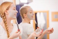 Mujer que se aplica con la máscara del fango de la arcilla del cepillo a su cara Imagenes de archivo