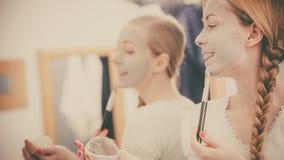 Mujer que se aplica con la máscara del fango de la arcilla del cepillo a su cara Fotografía de archivo libre de regalías