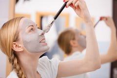 Mujer que se aplica con la máscara del fango de la arcilla del cepillo a su cara Foto de archivo