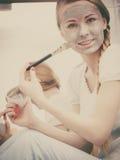 Mujer que se aplica con la máscara del fango de la arcilla del cepillo a su cara Imagen de archivo