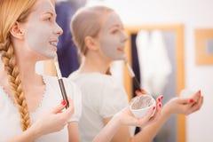 Mujer que se aplica con la máscara del fango de la arcilla del cepillo a su cara Imagen de archivo libre de regalías