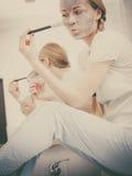 Mujer que se aplica con la máscara del fango de la arcilla del cepillo a su cara Foto de archivo libre de regalías