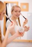 Mujer que se aplica con la máscara del fango de la arcilla del cepillo a su cara Fotografía de archivo
