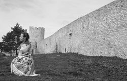 Mujer que se arrodilla al lado de una pared y de una torre de la fortaleza Foto de archivo libre de regalías