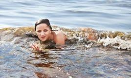 Mujer que se baña en la onda del mar imagen de archivo