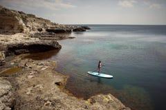 Mujer que se bate en tablero del SORBO en un mar foto de archivo