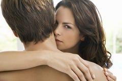 Mujer que se besa en el cuello del hombre Fotos de archivo
