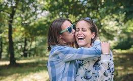 Mujer que se besa y que abraza a la risa femenina del amigo Imagenes de archivo