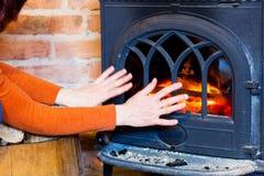 Mujer que se calienta las manos en el interior de la chimenea del fuego calefacción Foto de archivo