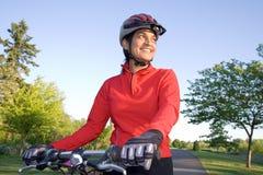 Mujer que se coloca al lado de la bicicleta - horizontal Foto de archivo libre de regalías
