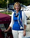 Mujer que se coloca al lado de un barco Imagen de archivo libre de regalías