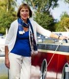 Mujer que se coloca al lado de un barco Foto de archivo libre de regalías