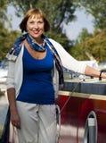 Mujer que se coloca al lado de un barco Imagen de archivo