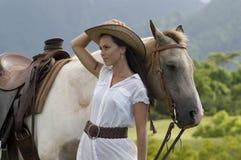 Mujer que se coloca al lado de un caballo imagenes de archivo