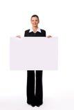mujer que se coloca al lado de una tarjeta en blanco Fotos de archivo libres de regalías