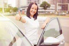 Mujer que se coloca al lado del coche con los pulgares para arriba Imagenes de archivo