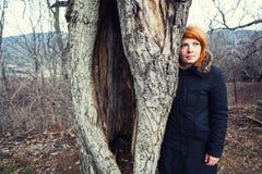 Mujer que se coloca cerca de árbol viejo Imagenes de archivo