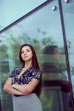 Mujer que se coloca cerca de la pared de cristal Imagen de archivo libre de regalías