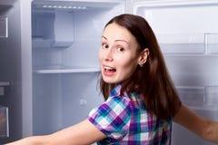 Mujer que se coloca cerca del refrigerador vacío abierto Foto de archivo