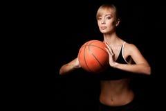 Mujer que se coloca con baloncesto Foto de archivo
