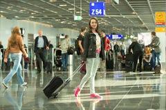 Mujer que se coloca con el bolso negro del viaje en el aeropuerto, Alemania Imágenes de archivo libres de regalías