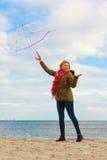 Mujer que se coloca con el paraguas transparente en la playa Fotografía de archivo