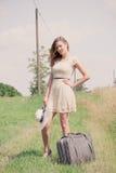 Mujer que se coloca con la maleta en un borde del campo foto de archivo libre de regalías
